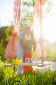 Couple kissing outdoors near the  swing — Stock Photo