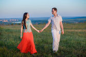 Couple on a cliff at sunset — Stock Photo