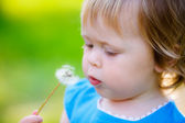 Girl blowing on a dandelion flower — Stock Photo