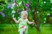 Girl among blooming lilacs — Stock Photo