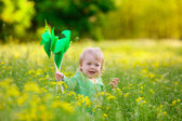 Child in a field with  pinwheel — Stock Photo