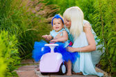 Mother with daughter on a toy car — Stok fotoğraf