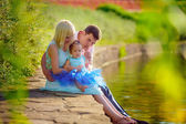 Family with a child sitting near the river — Stock Photo