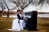 Girl in white dress posing near the piano — Stock Photo