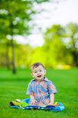 Junge auf gras zu sitzen — Stockfoto