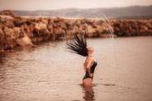 Chica salpicaduras de agua con el pelo — Foto de Stock