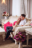 Pregnant woman with her husband  on the couch — Stock Photo