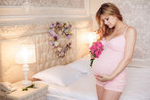Pregnant woman with a bouquet of roses — Photo