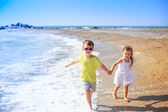 Beautiful kids running along the beach. — Stock fotografie