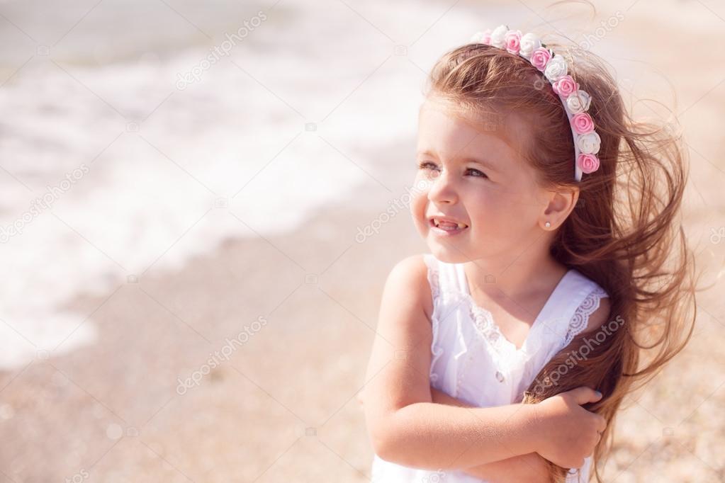 可爱的小女孩,在沙滩上散步的白色连衣裙