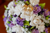 Wedding rings and beautiful bridal bouquet — Stock Photo