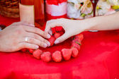 Newlyweds hands lay out   heart of strawberries — Stock Photo