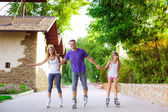 Family riding rollerblading on a summer day — Stock Photo