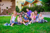 Family sitting on the grass with bikes — Stock Photo