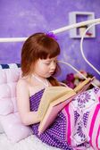 Adorable girl with a book on the bed — Stock Photo