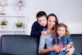 Mother with son and daughter sitting on the couch — Stock Photo