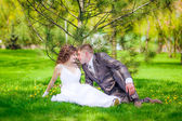 Newly-married couple sit on green grass — Stock Photo