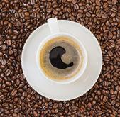 Kopje zwarte koffie over boon gedekt achtergrond — Stockfoto