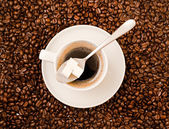 Cup of black coffee over bean covered background — Stock Photo