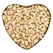Heart shaped box full of peanuts — Stock Photo