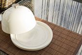 Ceramic salver with white dish over glass table — Stok fotoğraf
