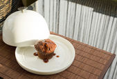 Chocolate muffin under the ceramic salver over white dish — Stock Photo