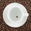 Ceramic cup with one coffee bean - Stock Photo