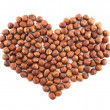 Heart shape made of hazelnuts isolated - Stock Photo