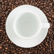 Ceramic cup and plate over coffee beans - Stock Photo
