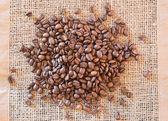 Coffee beans on tissue mat — Stock Photo