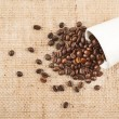 Cup full of coffee beans over hessian cloth — Stock Photo
