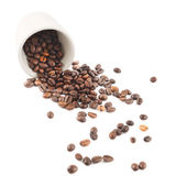 Spilled coffee beans from the cup isolated — Stock Photo