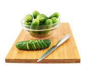 Slicing cucumber over a cutting board — Stock Photo
