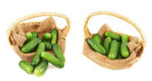 Wicker basket full of cucumbers isolated — Stock Photo