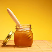 Wooden honey dipper in a honey jar — Stock Photo