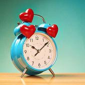 Reloj despertador con tres corazones sobre — Foto de Stock