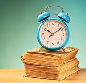 Alarm clock over the books — Stock Photo