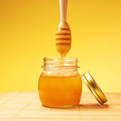 Honey jar with wooden dipper composition — Stock Photo