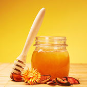 Honey jar, potpourri and wooden dipper — Stock Photo