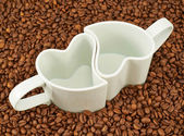 Two empty cups on coffee beans — Stock Photo