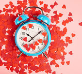 Alarm clock covered with red heart — Stock Photo