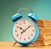 Alarm clock and old books — Stock Photo
