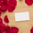 Card and rose petals with a blank space — Stock Photo #24369821
