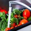 Stock Photo: Vegetables are washed in kitchen sink