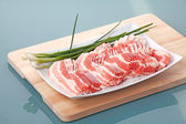 Sliced raw bacon on plate — Stock Photo