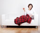Mädchen mit einem apfel auf dem sofa — Stockfoto