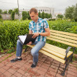 Portrait of a man sitting down on a bench — Stock Photo