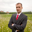Portrait of young businessman on a green meadow — Stock Photo