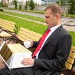 Photo: Businessmworking on laptop outdoor and drinking cup of coffee