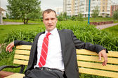 Young man in suit sitting on bench — Stock Photo